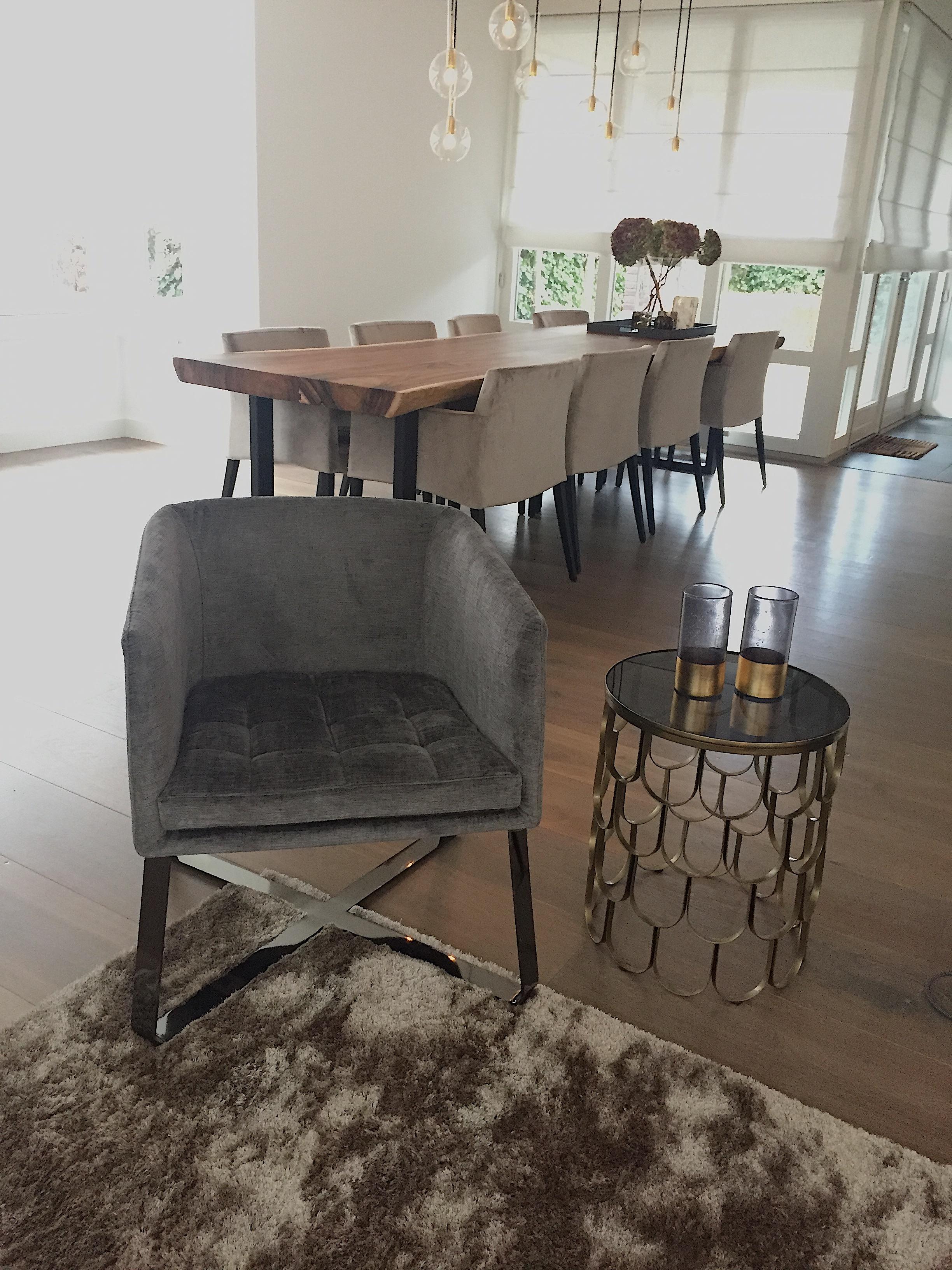 in de eethoek is gekozen voor een boomstamtafel gecombineerd met luxe stoelen in warm velours met daarboven een op maat gemaakte lamp